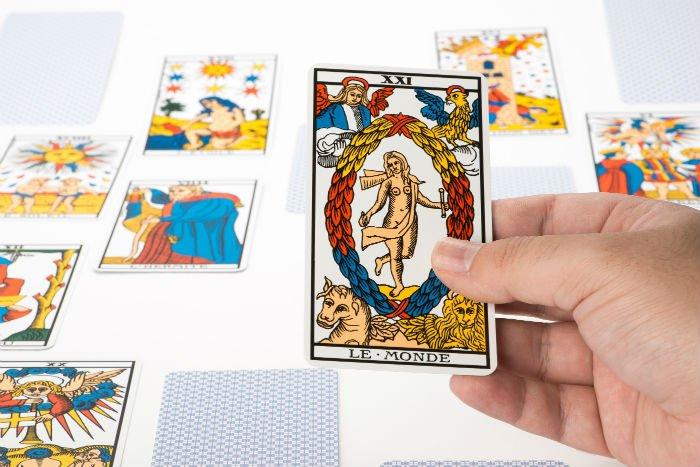 Fortune teller holding a le-monde tarot card